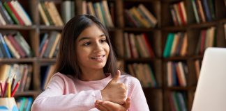 Smiling deaf school girl learning online class on laptop communicating with teacher by video conference call using sign language showing hand gesture during virtual lesson.